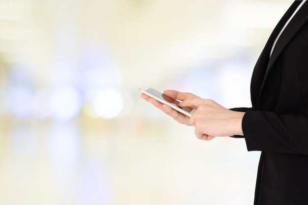 Business woman hands using smart phone over blur bokeh light background, business on phone
