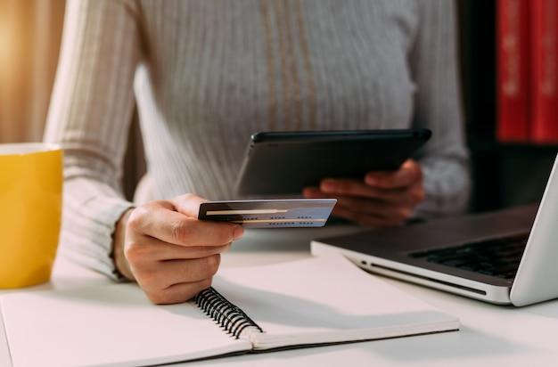 비즈니스 여자 손 스마트 폰을 사용하고 온라인 쇼핑 개념으로 디지털 레이어 효과 다이어그램으로 신용 카드를 들고