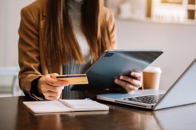 비즈니스 여성은 스마트폰을 사용하고 온라인 쇼핑 개념으로 디지털 레이어 효과 다이어그램이 있는 신용 카드를 들고 있습니다.