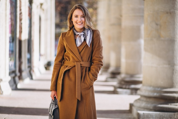 Business woman happy in coat in the street