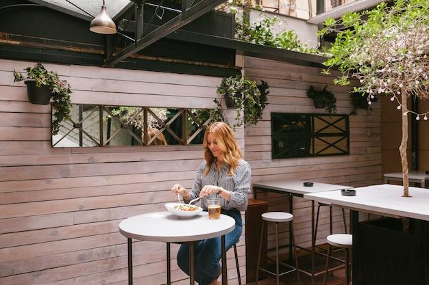 休憩と健康的な緑の食べ物を食べる女性実業家