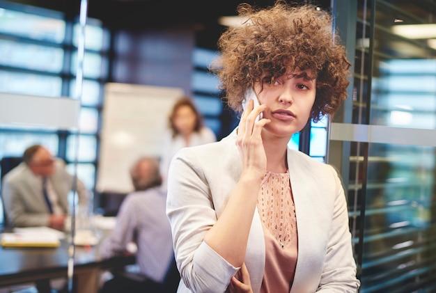 Деловая женщина разговаривает по телефону на работе