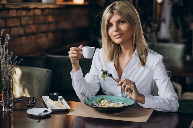 ビジネスの女性がカフェで昼食をとった