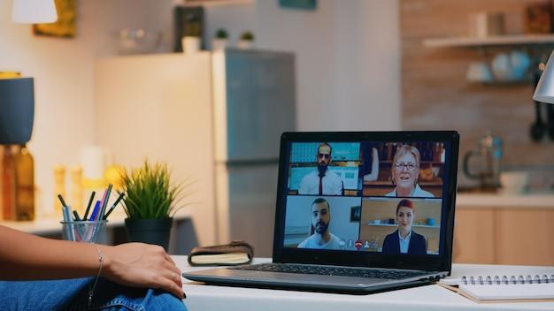 Donna d'affari che ha webinar studiando da casa utilizzando la tecnologia internet sul laptop a mezzanotte. signora che utilizza il notebook con la rete wireless che parla durante una riunione virtuale di notte facendo gli straordinari