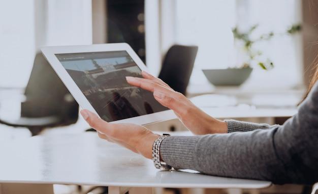 ビジネスの女性は手でタブレットを保持します。