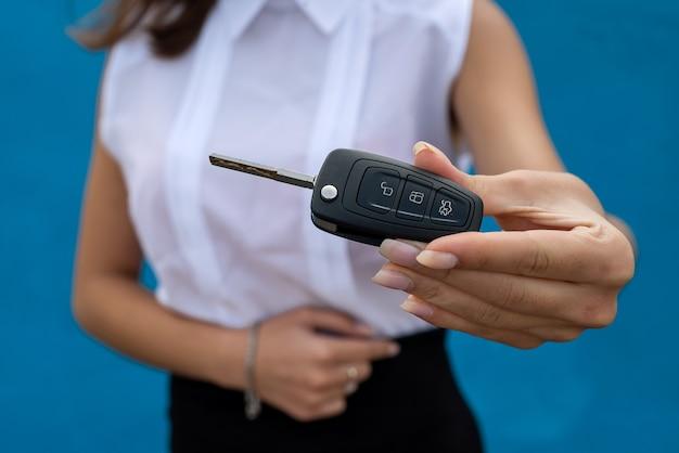 비즈니스 우먼은 파란색 배경에 격리된 자동차 키를 잡고 있습니다. 판매