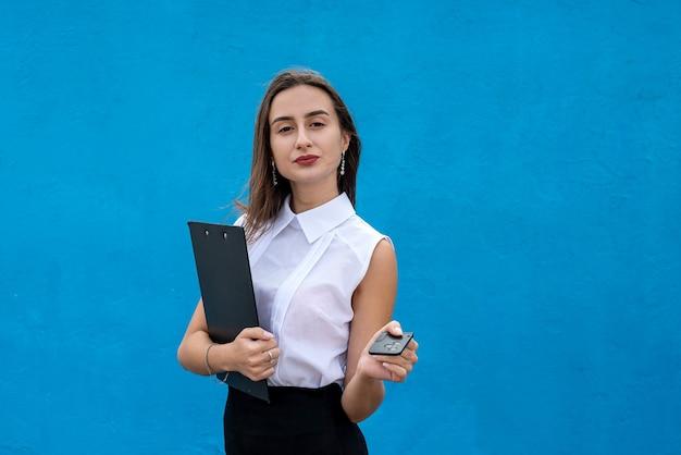 ビジネス女性は青い背景で隔離の車のキーを保持します。セール