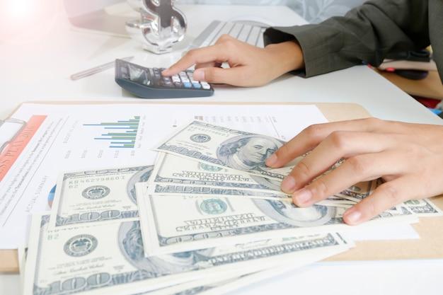 Деловая женщина держит деньги доллар с калькулятором на планшете как финансовую и стратегическую концепцию