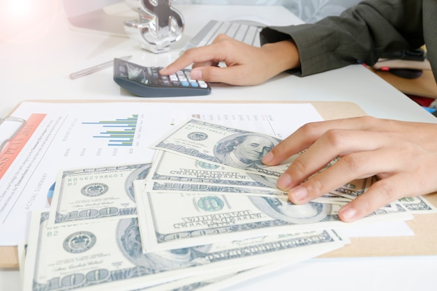 Business woman hold money dollar with calculator on tablet as financial  and strategy concept