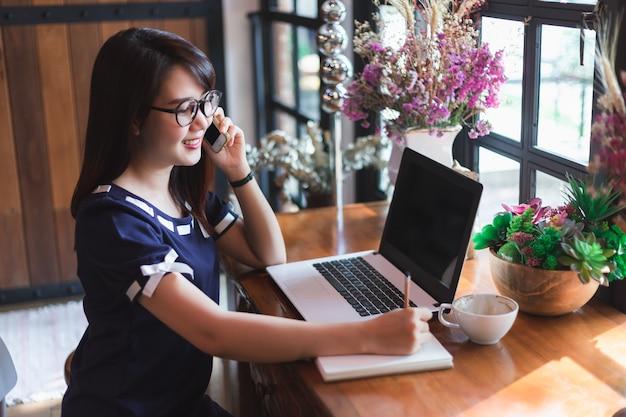 ビジネスの女性がピックアップホールドコーヒーショップでラップトップコンピュータで作業しているスマートフォン