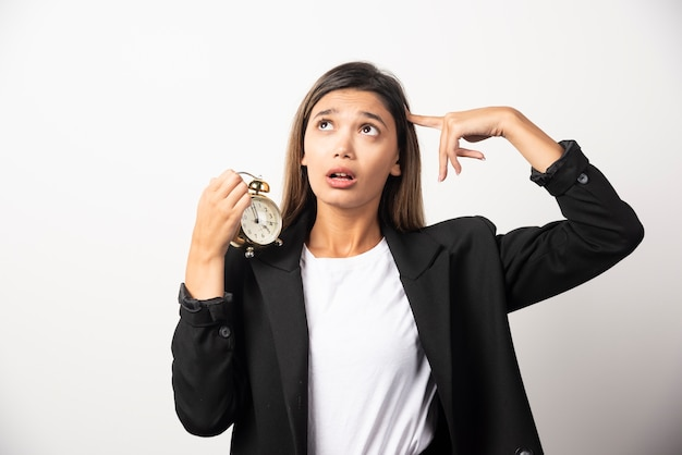 Business woman holding an alarm clock on white wall.