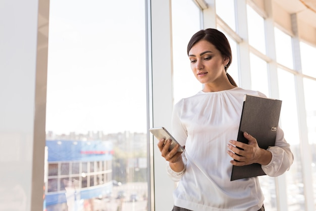 Business woman holding binder and looking at smartphone