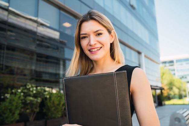 Business woman holding clipboard and standing outdoors.