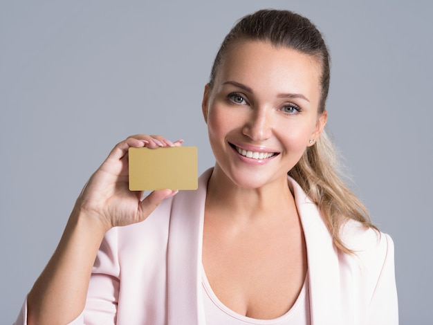 Business woman holding credit card against her face isolated studio portrait