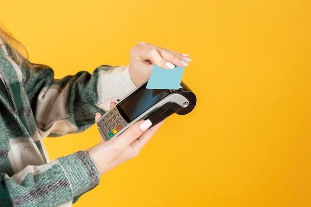 Деловая женщина, держащая кредитную карту и смотрящую в камеру.