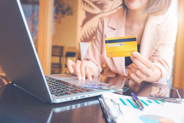신용 카드를 들고 온라인 쇼핑을 하는 노트북을 사용하는 비즈니스 여성. 프리미엄 사진