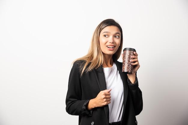 カップを保持し、白い壁にポーズをとるビジネス女性。