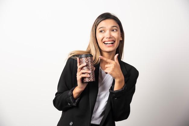 Donna di affari che tiene tazza e posa sul muro bianco.