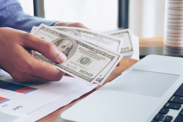 Business woman holding dollar banknote in hand at office
