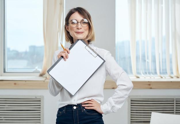 창 근처 문서와 폴더를 들고 사업 여자