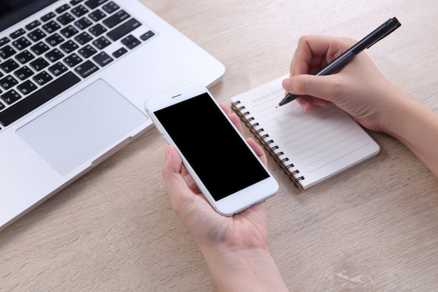 Business woman holding mockup smartphone with writing on note book