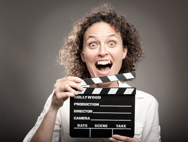 Business woman holding a movie clapper board on a grey wall