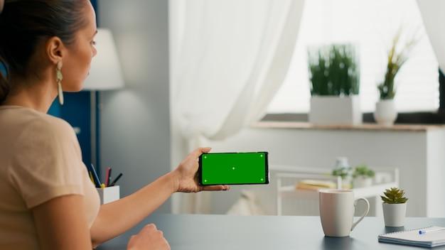 사무실 책상에 앉아 복사 공간을 위해 모의 녹색 화면 크로마 키가 있는 전화를 들고 있는 비즈니스 여성. 격리된 가제트를 사용하여 인터넷에서 검색하는 소셜 미디어 인플루언서