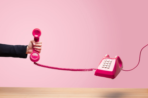 Business woman holding the red phone