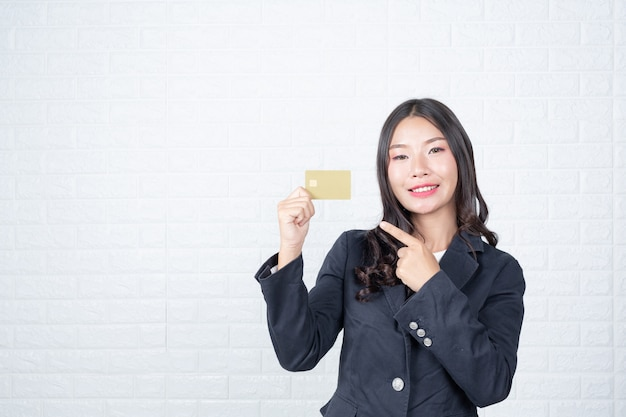 Business woman holding a separate cash card, white brick wall made gestures with sign language.