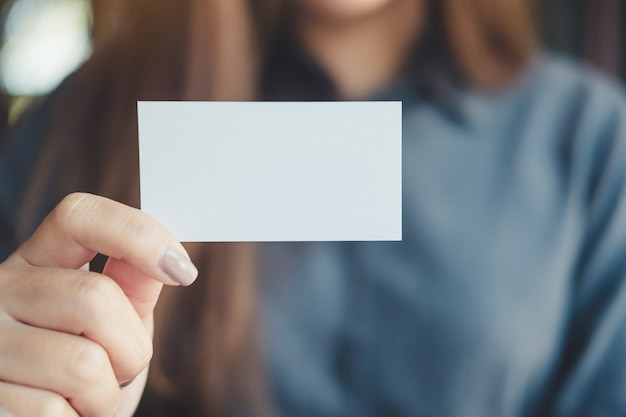 Business woman holding and showing empty business card in office