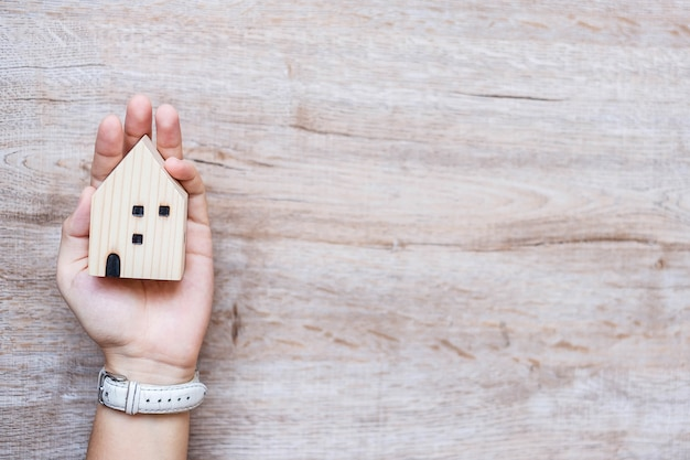 Business woman holding wooden house model