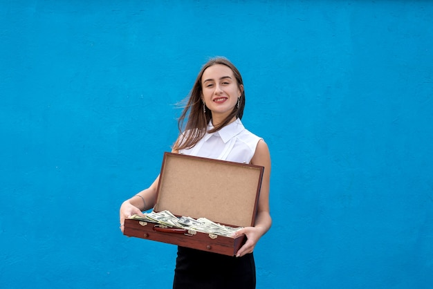 Business woman holding wooden suitcase full dollars bill after success deal or big winner on blue background