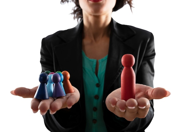 Business woman holds colorful wooden toy shaped as person. concept of business teamwork and leadership. isolated on white background