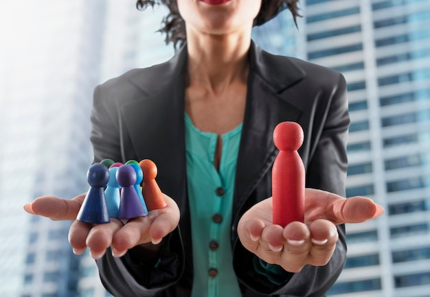 Business woman holds colorful wooden toy shaped as person. concept of business teamwork and leadership