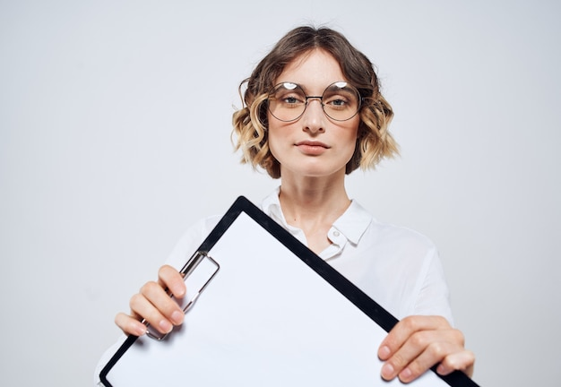 Business woman holds in her hands a folder with a white sheet on a light background mockup