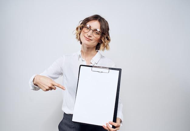 Деловая женщина держит в руках папку с белым листом на свету