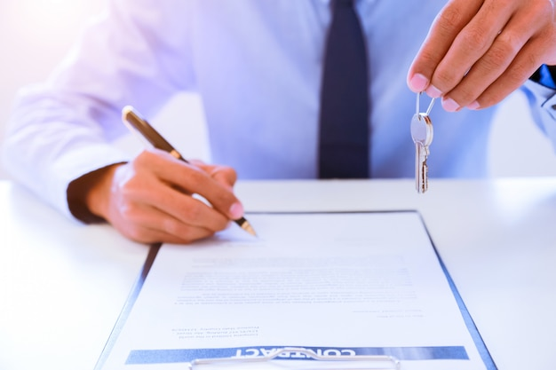 Business woman holds key and contract in hands.