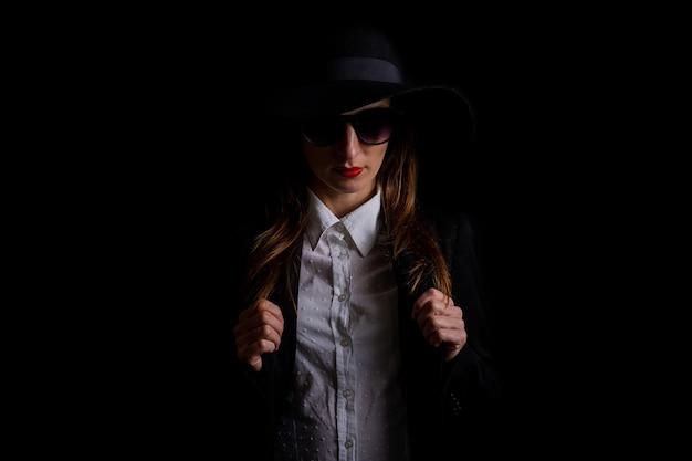 Деловая женщина в черной шляпе, очках на черном.