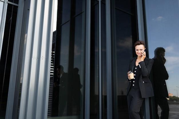 ビジネスセンターのガラスの建物の上に黒のスーツのビジネスウーマン