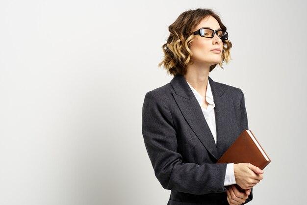 Деловая женщина в классическом костюме с ноутбуком в руке и очках на лице copy space. фото высокого качества