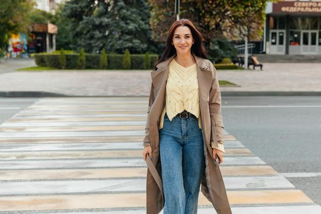 Деловая женщина в длинном плаще переходила дорогу на улице в солнечную погоду