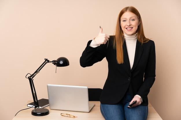 Деловая женщина в офисе, давая пальцы вверх жест