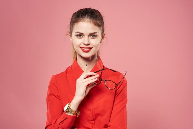 Деловая женщина в красной рубашке элегантный розовый фон с ноутбуком в руках. фото высокого качества