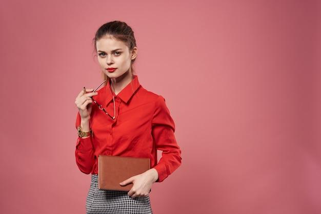 彼女の手にノートを持った赤いシャツのエレガントなピンクの背景のビジネス女性。高品質の写真