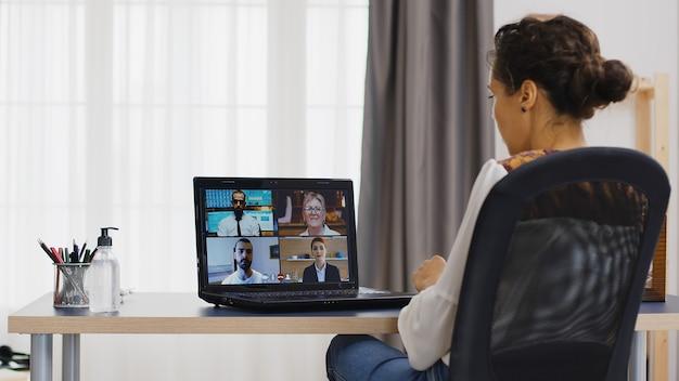 Деловая женщина в удаленном видеозвонке на ноутбуке из домашнего офиса.