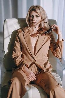 明るい部屋の肘掛け椅子に座ってスーツを着たビジネスウーマン
