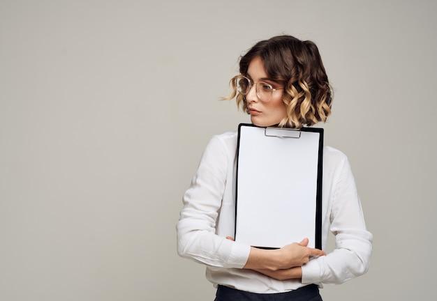 Деловая женщина в костюме с чистым листом бумаги на светлом фоне с копией пространства. фото высокого качества