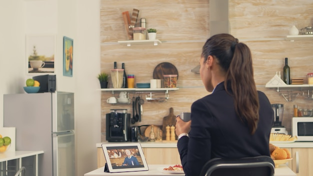 아침 식사를 하는 동안 아버지와 영상 통화를 하는 비즈니스 여성. 최신 온라인 인터넷 웹 기술을 사용하여 웹캠 화상 회의 앱을 통해 친척, 가족, 친구와 채팅