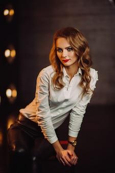 긴 머리와 빨간 립스틱과 어두운 studio.model의 내부에 램프를 굽기의 배경에 흰색 셔츠에 비즈니스 여자.
