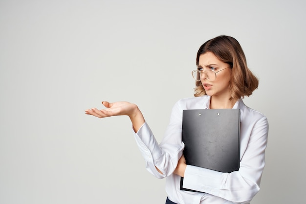 그녀의 손에 문서 감정 작업에 폴더와 흰 셔츠에 비즈니스 우먼